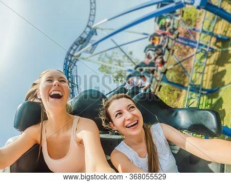 Two Happy Girls Having Fun On Rollercoaster