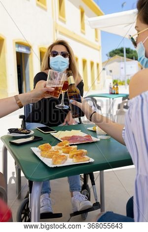 Mature Woman Using A Wheelchair And A Surgical Mask Doing A Toast With Other People At An Outdoor Ba