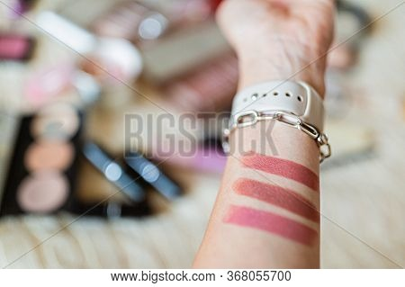 Female Hand Holding Lipsticks And Color Swatches Painted On Hand. Beauty Blogger Making Lipstick Swa