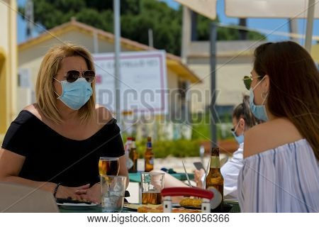 Women Using Surgical Masks And Sunglasses Sitting At An Outdoor Bar Terrace With Beers And Snacks