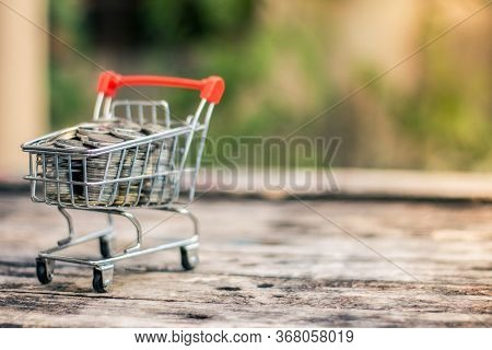 Close Up Coins And Receipts Paper On Mini Shopping Cart With Natural Light Background (business And