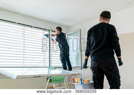 A Professional Cleaning Team In An Apartment Cleaning Windows And Blinds With A Vacuum And Other Cle