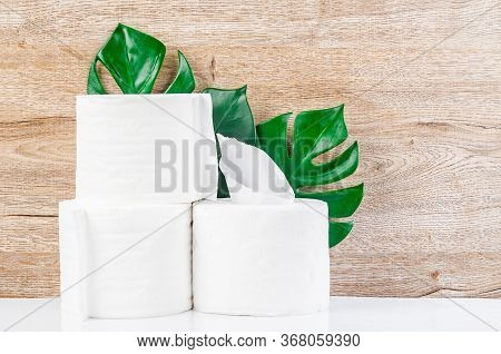 White Kitchen Paper Towel, Toilet Paper, Paper Tissues, Cotton Pads And Green Leaves On A Wooden Tab