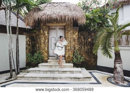 Asian Woman With Black Curly Hair Enjoying In Private Villa In Canggu. Wearing White Light Tunic, Ba