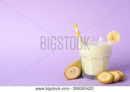 Glass Of Banana Milkshake On Violet Background. Summer Drink