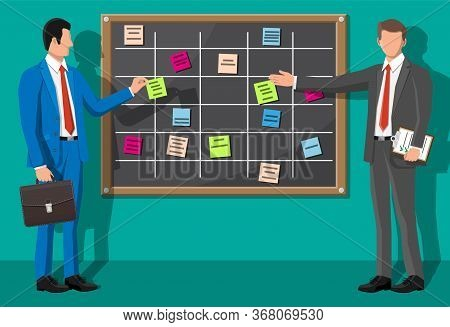 Scrum Agile Board And Businessman. Bulletin Board Hanging On Wall Full Of Tasks On Sticky Note Cards