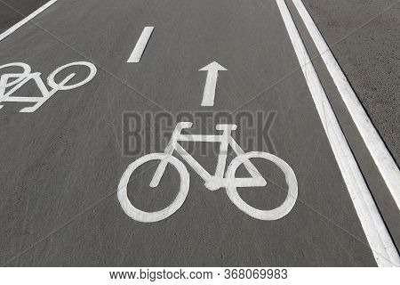 Painted Signs On Asphalt For Bicycle Dedicated Lanes. Bike Lane On The Road. A Separate Bike Path In