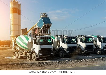 Row Of Many Modern Big Mixer Trucks Parked Against Mobile Temporary Concrete Plant Factory At New As