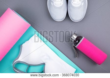 Top View Of White Sport Shoes Sneakers Blue Pink Yoga Mat, Sport Bra Top, Glass Water Bottle On Past