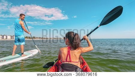 Couple kayaking and paddle boarding fitness man in ocean Paddleboard beach people on stand-up paddle boards surfing in Tourists kayakers woman and man enjoying SUP kayak watersport Keys, Florida, USA.