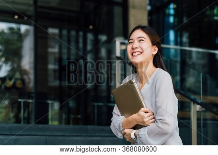 One Successful And Happy Young Adult Business Woman Holding A Laptop With Smile. Professional Female