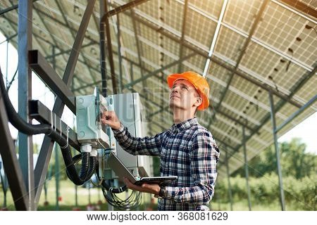 Male Engineer In Helmet And With Laptop Pushing Button At The Electrical Equipment On Solar Power St
