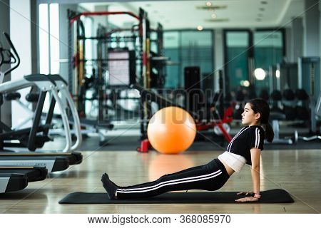 Young Beautiful Girl Warming Up And Doing Some Push Ups A The Gym