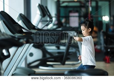 A Little Girl Is Running On The Treadmill. Children's Sport Concept