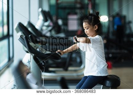 A Little Girl  Looks At Smart Watch After Training In Gym. Healthy Concept. Female After Workout Ses