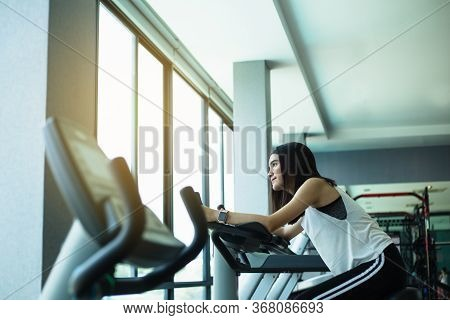 Fit Young Girl Using Exercise Bike At The Gym. Fitness Female Using Air Bike At Gym.