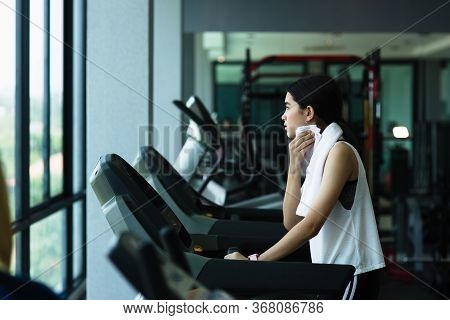 Side View Of Beautiful Girl Running On Treadmill At Gym