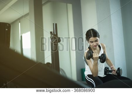 Young Beautiful Girl Doing Exercises With Dumbbell In Gym.
