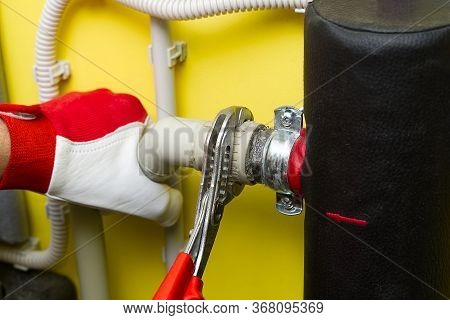 Hands Repairing The Plumbing Pipes Of Home Heating System. Plumber Tightens The Connection With A Wr