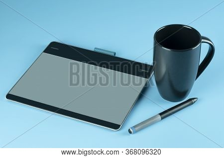 Workplace Or Workspace Of Graphic Designer, Small Graphic Tablet With Digital Pen And Black Cup Of C