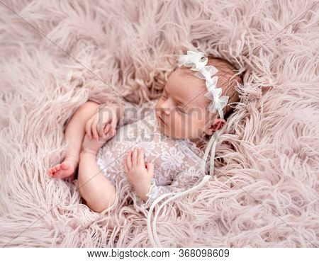Charming newborn wearing lace suit and diadem