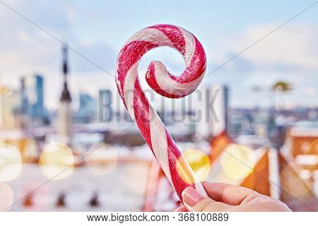 Close Up View Of Striped Candy Cane Lollipop In Hand Against Old City Of Tallinn. Iconic View Of Tal