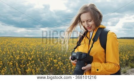 Half-length Portrait Of Content Woman Looking Through Recent Images On Dslr Camera Standing On Field