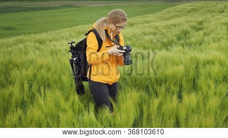 Portrait Of Woman Standing On Green Field Looking Through Recent Pictures On Her Dslr Camera, Half T