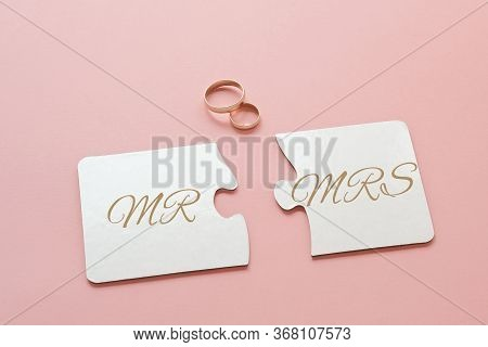 Two White Disconnected Puzzles With The Inscription Mr. And Mrs. And Two Gold Wedding Rings On A Pin