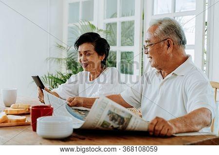 Senior Asian Couple Having Breakfast Together In Dinner Room. 70s Retired Elderly Man Reading Newspa