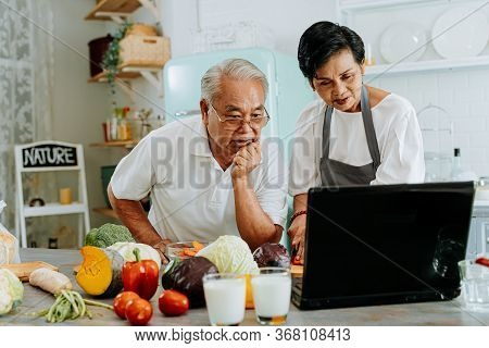 Senior Asian Couple Using A Laptop While Cooking In Kitchen At Home. 70s Elderly Man And Woman In Re
