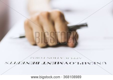 Close-up Of A Person's Hand Filing Social Security Benefits Application Form.  Concept Of Coronaviru