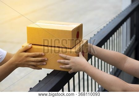 Courier Service Is Delivering The Brown Box To The Recipient. The Shipping Company Delivers The Good