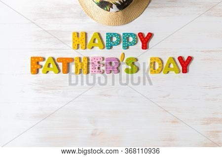 Happy Father's Day Inscription Of Colorful Wooden Letters And Summer Hat On Vintage Wood Background.