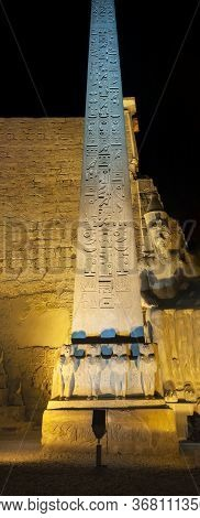 Large Tall Ancient Egyptian Obelisk At The Temple Of Luxor With Hieroglyphic Carvings Lit Up In Nigh