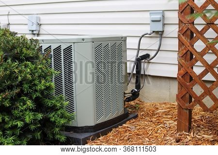 An Outdoor Air Conditioning Unit  By A Home