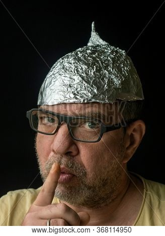 Strange man in a protective foil cap and glasses. Conspirology and fake news concept