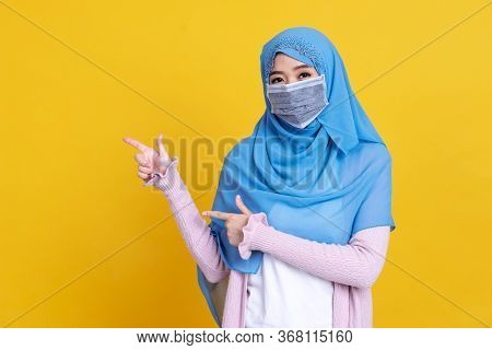 Photo Of Islamic Woman In Hijab Headscarf Wearing Mask With Oriental Makeup Pointing Finger On Copy