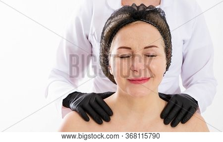 Aging And Skin Care Concept - Portrait Of Middle Age Woman And The Hands Of A Dermatologist On Her S