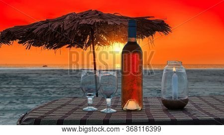 Tropical Sunny Beach Party At Sunset With Sun Umbrellas And Wine Glasses In Goa, India