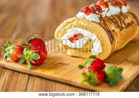 Biscuit Roulade With Mascarpone Cream, Strawberries And Chocolate, Laid Out On A Wooden Board.