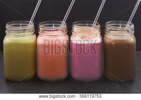 Different Flavors Of Whey Protein Shake - Banana Strawberry Blackberry Coffee In A Drinking Cup