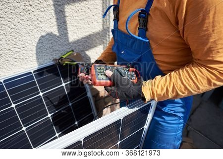 Man Engineer Installing Solar Photovoltaic Panel System On Roof Of Modern House. Electrician Checkin