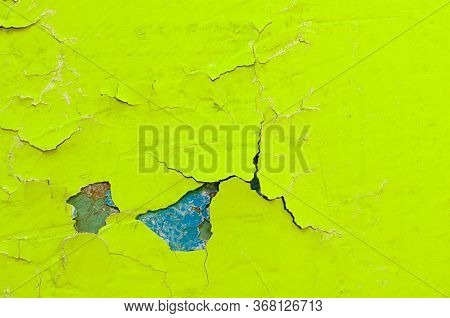 Texture peeling paint background - light yellow and turquoise peeling paint on the old rough concrete surface, peeling paint texture. Peeling paint background, peeling paint bright surface