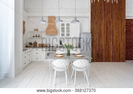 Front View Of White Kitchen With Modern Interior, Cabinets, New Furniture, Dining Table Setting, Gas