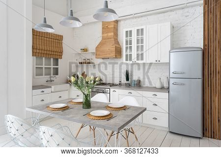 Side View Of Modern Kitchen At New Apartment With White Interior, Dining Table Setting, Gas Stove, R