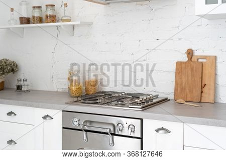 Concept Of Kitchen Interior In Bright Modern Style. White Furniture, New Gas Stove, Oven, Wooden Cab