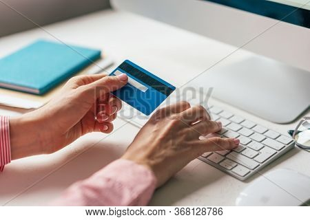 Close-up Of A Credit Card In Hands Typing On A Keyboard. Work From Home. Online Shopping With Home D