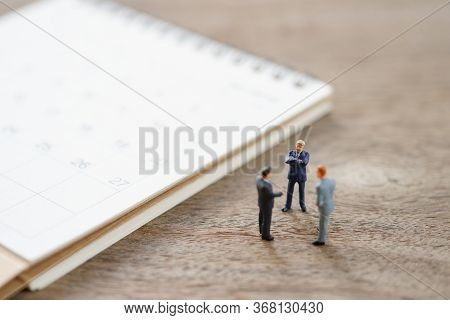 Miniature People Businessmen Standing On White Calendar Using As Background Business Concept And Fin