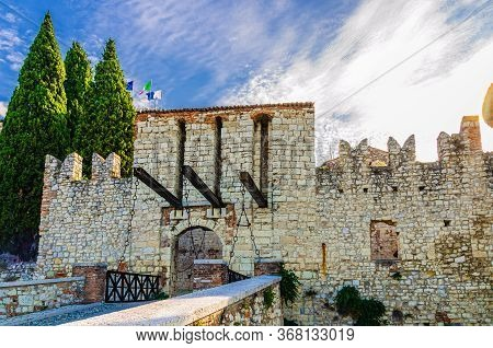 Brescia, Italy, September 11, 2019: Stone Wall With Merlons And Drawbridge Gate Of Medieval Castle C